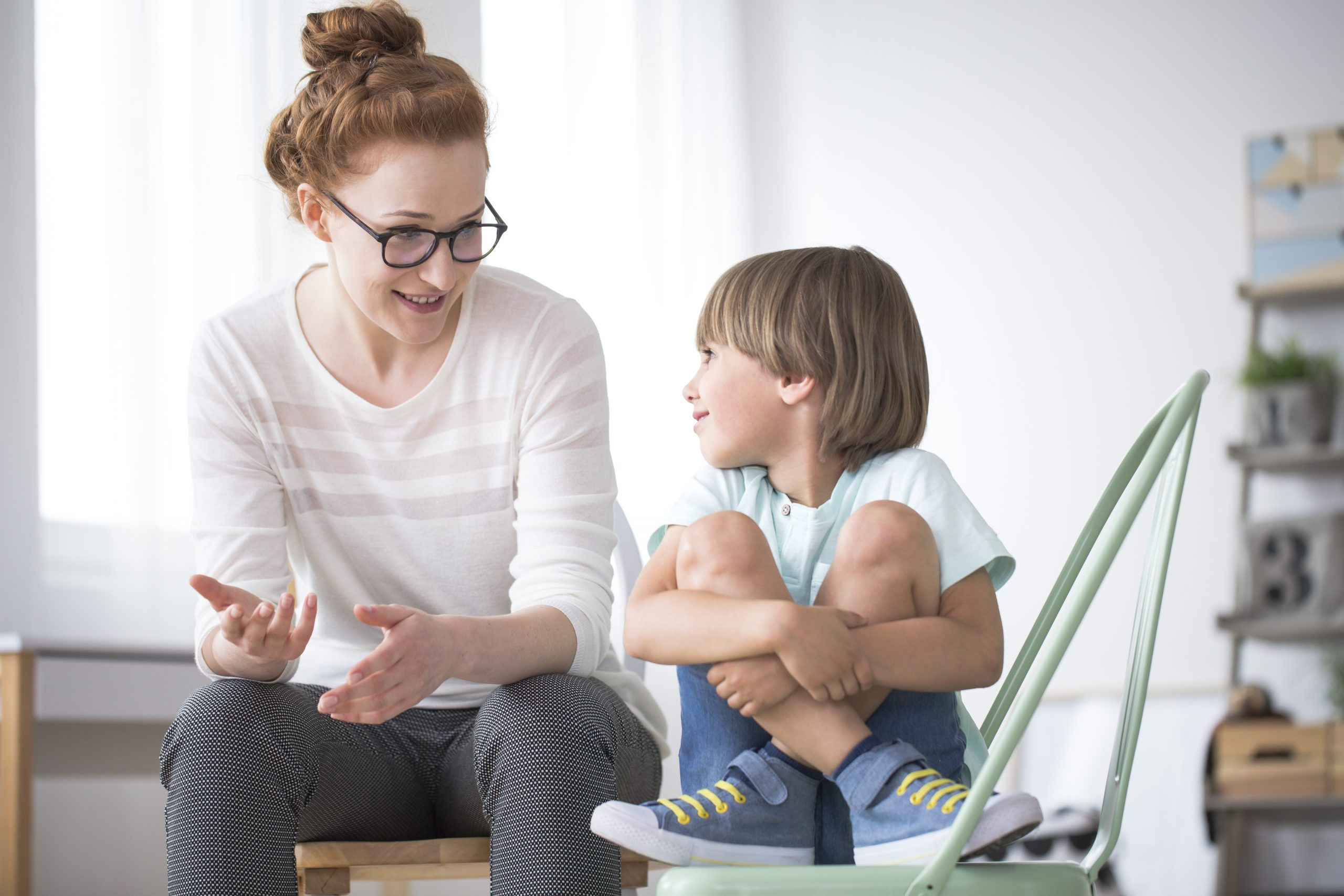 Mother talking to her smiling son sitting on green chair about school